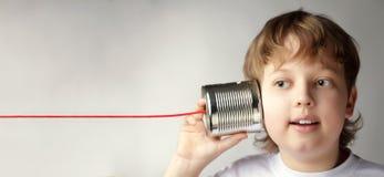 在锡罐电话的愉快的男孩戏剧,男孩附有了一个电话 库存图片