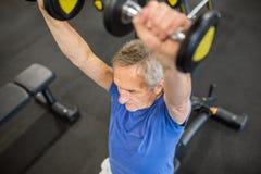 在锤子力量机器的老人举的重量 免版税库存照片