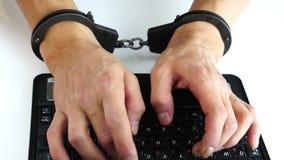 在键入在便携式计算机上的手铐的男性手,预防犯罪,黑客攻击,信息技术,处罚 股票视频