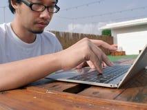 在键入在膝上型计算机键盘的亚裔人的手上的选择聚焦  免版税库存图片