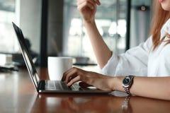 在键入在膝上型计算机键盘的女商人的手上的选择聚焦  生活方式轻松的概念 免版税库存照片