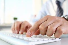 在键入在银色键盘的衣服的男性胳膊 免版税库存照片