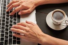 在键盘和咖啡的手 库存图片