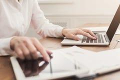 在键盘和片剂接近的妇女手 库存图片