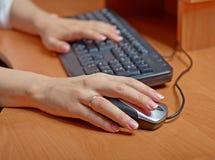 在键盘和老鼠的女性手 免版税库存照片