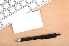 在键盘的空白的名片在办公室桌上 免版税库存照片