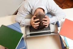 在键盘的被注重的学生或商人头 免版税库存照片