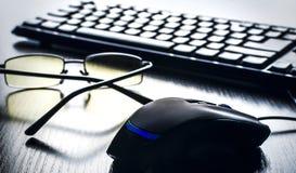 在键盘附近的黑计算机老鼠 免版税库存图片