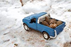 在锯木厂的蓝色玩具卡车 黏附在随风飘飞的雪和锯木屑运载的冷杉球果在车身背后 免版税库存图片