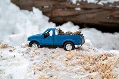 在锯木厂的蓝色玩具卡车 黏附在随风飘飞的雪和锯木屑运载的冷杉球果在车身背后 库存照片