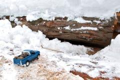 在锯木厂的蓝色金属玩具卡车 黏附在随风飘飞的雪和锯木屑运载的冷杉球果在车身背后 库存图片