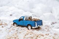 在锯木厂的蓝色金属玩具卡车 黏附在随风飘飞的雪和锯木屑运载的冷杉球果在车身背后 免版税图库摄影
