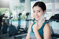 在锻炼以后的亚洲少妇饮用水在体育俱乐部 免版税库存图片