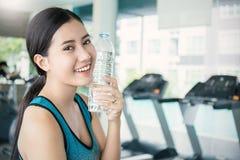 在锻炼以后的亚洲少妇饮用水在体育俱乐部 库存照片