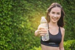 在锻炼以后的亚洲少妇饮用水 免版税库存图片
