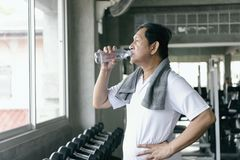 在锻炼以后的亚洲老人渴饮用水在fitnes 库存照片