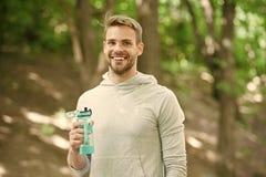 在锻炼以后的运动员满意的面孔举行瓶关心水合作用身体 在巨大锻炼以后的刷新的维生素饮料 ? 库存图片