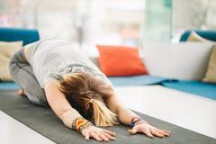 在锻炼席子的健身女性执行的瑜伽儿童姿势在健身房 免版税图库摄影
