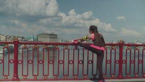 在锻炼期间的女性使兴奋肌肉在城市 影视素材