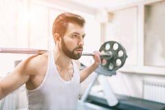 在锻炼期间的肌肉有胡子的人在健身房 做举重的爱好健美者 关闭年轻运动女性 库存照片