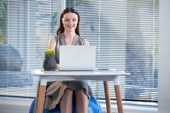 在锻炼球的女性行政开会,当使用膝上型计算机在书桌时 库存照片