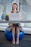 在锻炼球的女性行政开会,当工作在书桌时 免版税库存图片