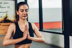 在锻炼锻炼前的美女坐的瑜伽培养手 库存图片