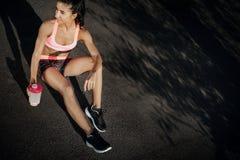 在锻炼oudoor以后的有吸引力的健身少妇休息 举行蛋白质震动的运动的妇女在tranning以后 库存照片