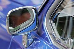 在镀铬物框的汽车镜子在一辆蓝色汽车 免版税库存图片