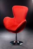 在镀镍层的钢腿的红色丝绒位子在黑背景的演播室 舒适的办公室椅子红色 库存图片