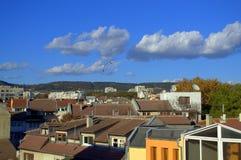 在镇屋顶和明亮的天空的生动的看法 库存照片
