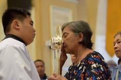 在镇庆祝期间,天主教妇女给亲吻的圣洁圣体匣的罕见的机会 图库摄影