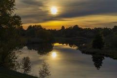 在镇静河水表面反映的日出 免版税库存照片