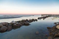 在镇静海湾的岩石防波堤在日落 免版税库存图片