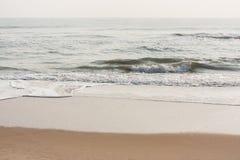在镇静海滩的泡沫似的波浪 图库摄影
