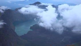 在镇静湖的惊人的天线4k视图在天空的巨大的远足的石山脉白色云彩之间在Rinjani,印度尼西亚 股票视频