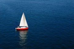 在镇静蓝色海的一个孤立白色风帆 库存图片