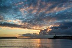 在镇静水海洋的美丽的充满活力的日出天空有lightho的 免版税库存照片