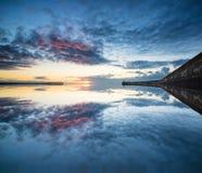 在镇静水海洋的美丽的充满活力的日出天空有lightho的 免版税库存图片