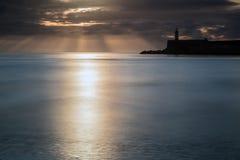 在镇静水海洋的美丽的充满活力的日出天空有lightho的 库存图片
