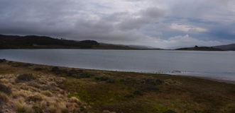 在镇静水风景上的风雨如磐的天空 免版税库存图片
