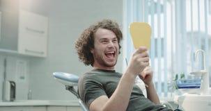 在镜子前面的一名微笑的年轻患者在一个口腔卫生做法以后的牙齿诊所室,他检查了他的 股票录像