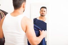 年轻在镜子前面的人尝试的衬衣 免版税库存照片
