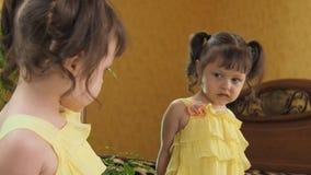 在镜子前面的小女孩咬住她的嘴唇 一件黄色礼服的漂亮的孩子由镜子 有尾标的女孩 影视素材