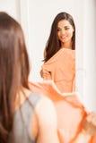 在镜子前面的尝试的衣裳 图库摄影
