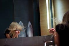 在镜子前面的年轻白肤金发的妇女在有迪斯科镜子球的休息室 免版税图库摄影