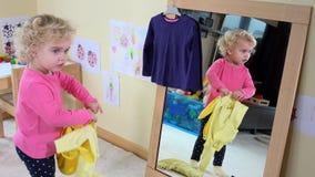 在镜子前面的逗人喜爱的女孩措施衣裳在家 影视素材