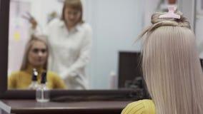 在镜子反映的被弄脏的美发师妇女做发型 股票录像