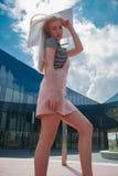 在镜子大厦附近的白肤金发的女孩 免版税库存图片