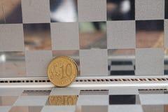 在镜子的欧洲硬币反射在木竹桌背景衡量单位的钱包谎言是10分 免版税库存图片